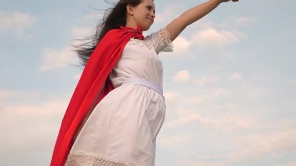 gyönyörű szuperhős lány állt a pályán egy piros köpenyt, köpenyt csapkodott a szél. lány álma válik szuperhős. Lassított. fiatal nő játszik egy piros köpenyt, az álmok kifejezése.