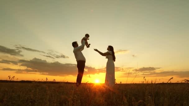 Táta má šťastný malou dceru v jejích rukou a dává své matce. dcera si hraje s mámou a tátou na slunci. pojem rodina a dětství. šťastná rodina v parku v paprscích zapadajícího slunce