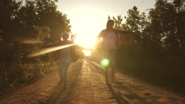 Hiker Girl. children travelers. teen girls travel and hold hands. happy girls travelers with backpacks run along country road holding hands in rays of the bright sun. concept of sports tourism and