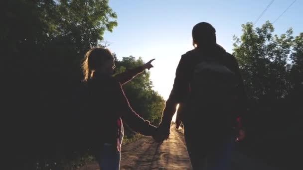 Hiker Girl. dívky v pubertě cestují a drží se za ruce. dětské cestovatele. dívky s batohy jsou na venkovské silnici na slunci. koncepce sportovního turismu a cestování.
