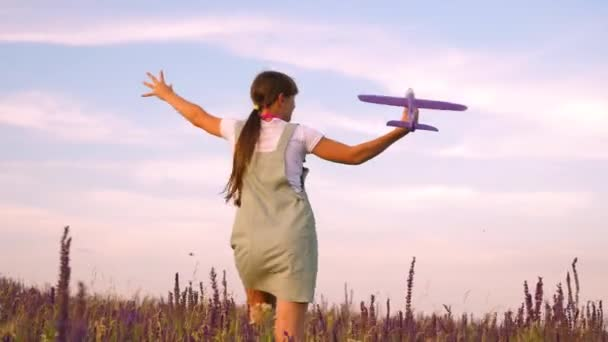 Happy girl runs with a toy airplane on a flower field. children play toy airplane. teenager dreams of flying and becoming a pilot. the girl wants to become a pilot and astronaut.