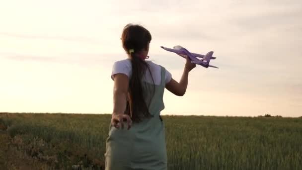 Boldog lány fut egy játék sík a búza területén. gyerekek játszanak játék repülőgép. tizenéves álmok repülési és válás pilóta. a lány akar válni a pilóta és az űrhajós.