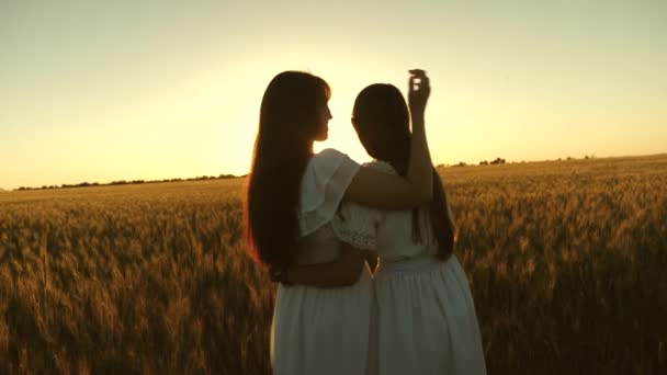 Mom gently hugs daughter against backdrop of a beautiful sunset. happy family concept. adult daughter in arms of her mother in a field in the rays of the sun. mom strokes her daughters hair.