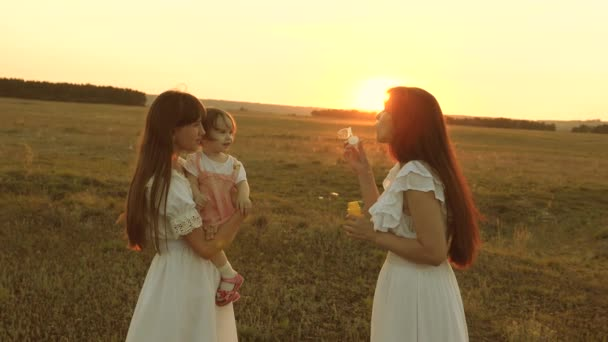 Daughters rejoice and smile, bubbles fly in park at sunset. Slow motion. Happy mother playing with children blowing soap bubbles. concept of a happy family. child, sister and mother play at sunrise.