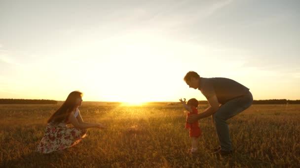 malá dcerka jde od táty k mamince na slunci. Šťastná mladá rodina s dětmi v letním terénu. Zdravá matka, otec a dceruška si spolu užívají přírodu. Zpomaleně.