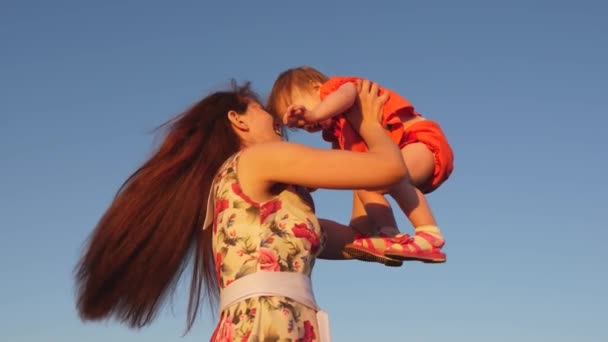 Mutter wirft ihre Tochter in den Himmel. Mutter spielt mit kleinem Kind vor blauem Himmel. glückliche Familie spielt am Abend gegen den Himmel. Mutter wirft das Baby hoch, Baby lächelt. Zeitlupenfilme.