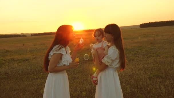 Töchter freuen sich und lächeln, Blasen fliegen bei Sonnenuntergang im Park. zeitlupe. Glückliche Mutter spielt mit Kindern blasen Seifenblasen. Konzept einer glücklichen Familie. Kind, Schwester und Mutter spielen bei Sonnenaufgang.