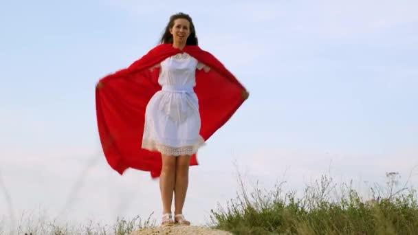 lány bolondozás körül állt a területen egy piros köpenyt, játék szuperhős. vidám nő játszik a piros köpenyt, az álmok kifejezése. lány álma válik szuperhős. Lassított mozgás.