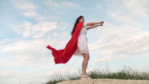 vidám nő játszik a piros köpenyt, az álmok kifejezése. lány álma válik szuperhős. lány bolondozás körül állt a területen egy piros köpenyt, játék szuperhős.