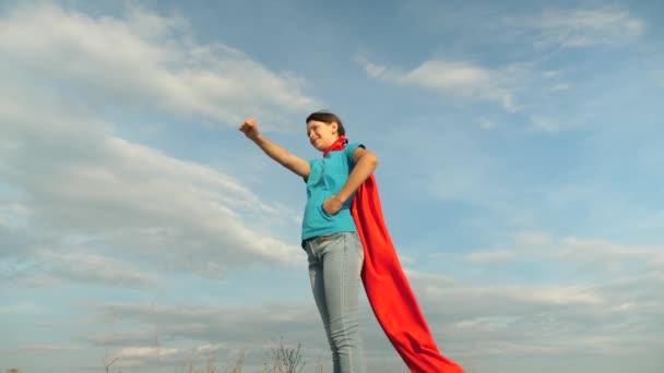 gyönyörű lány szuperhős állva mezőjében piros köpeny, Palást-szél csapkodott. Lassú mozgás. közelről. lány álma válhat szuperhős. fiatal lány állt egy piros köpenyt kifejezés az álmok.