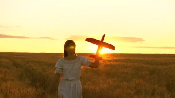 Boldog lány fut egy játék repülőgépet egy virág mező. gyerekek játszanak játék repülőgép. tizenéves álmok repülési és válás pilóta. a lány akar válni a pilóta és az űrhajós.