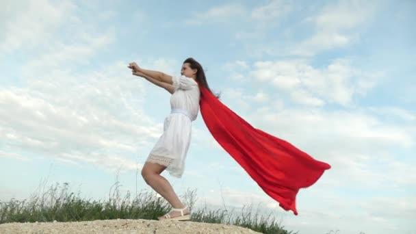 donna allegra gioca in un mantello rosso con espressione di sogni. ragazza sogna di diventare un supereroe. ragazza scherzando in piedi su un campo in un mantello rosso, giocando supereroe.