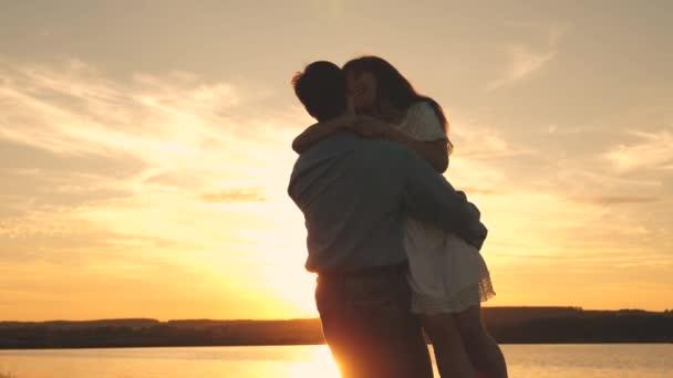 Šťastný muž a děvče, večer v letním parku. Milující muž a žena tančí v jasných slunečních paprscích na pozadí jezera. Mladí manželé tančí při západu slunce na pláži.