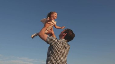 Dad throws up a happy daughter in the blue sky. Father and little child play, laugh and hug together. Happy family travels. Baby in the arms of the parent. Dad day off. The concept of a happy family.