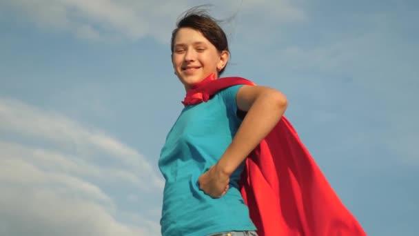 teen ragazza supereroe in piedi sul campo in un mantello rosso, mantello svolazzanti nel vento. Rallentatore. ragazza sogna di diventare un supereroe.