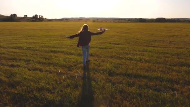 lány akar válni pilóta és űrhajós. Lassított. tizenéves álmok repülő-és válás pilóta. Boldog lány fut egy játék repülőgép a területen a naplementekor. gyerekek játszanak játék repülőgép.