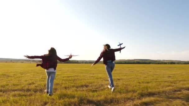 Álmok-ból repülés. Boldog gyermekkori koncepció. Két lány játszani egy játék sík naplementekor. Gyermekek a háttérben a nap egy repülőgép a kezében. A gépen játszó gyerekek sziluettje