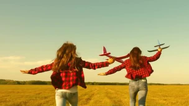 děti hrají hrací letadlo. Teenageři se chtějí stát pilotem a astronautem. Šťastné dívky jezdí s hračkářkou při západu slunce na hřišti. pojetí šťastného dětství. Děvčata sní o létání a stávkách pilotem.