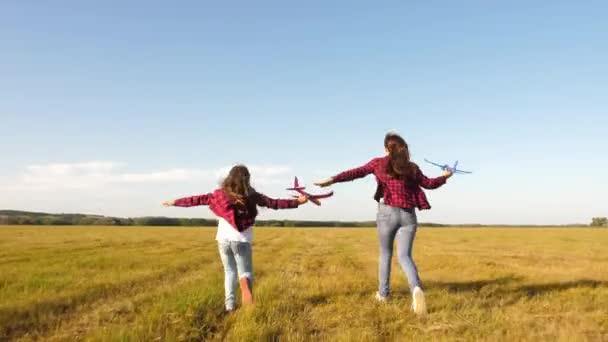gyerekek játszanak játék repülőgép. tinédzserek akarnak válni pilóta és űrhajós. Boldog lányok futni játék sík naplementekor a területen. egy boldog gyermekkor koncepcióját. Lányok álma a repülő-és válás pilóta.