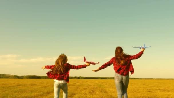 Lányok álma a repülő-és válás pilóta. gyerekek játszanak játék repülőgép. tinédzserek akarnak válni pilóta és űrhajós. Boldog lányok futni játék sík naplementekor a területen. a boldog gyermekkor fogalma.