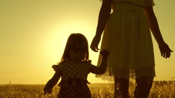 Mom walks across the field with a small child at sunset. daughter holds moms hand, a happy family walks in evening out of town. mother and baby are resting in park. child plays with mother in meadow.