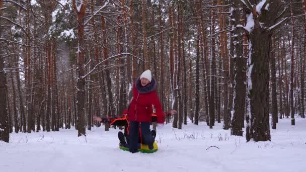 Rodina si o vánočních svátcích hraje v zimním parku. Šťastné děti a otec zimní sáňkování ve sněhu a mávání. děti se smějí a radují. Zpomal. Koncept šťastné rodiny.