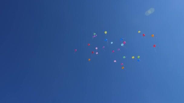 krásné barevné balónky létají na obloze, červená modrá žlutá oranžová růžová. Ve vzduchu létá mnoho barevných balónků. Oslava a narozeninová koncepce. Koncept krásné dovolené.