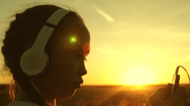 girl travels and listens to music in the warm sun. teen girl listening to music and watching the sunset. Happy girl dancing in headphones in the rays of a beautiful sunrise in the park.