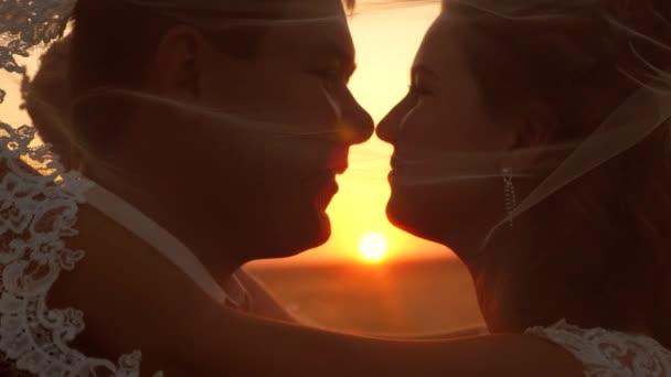 romantický zamilovaný pár při západu slunce. Koncept šťastné rodiny. nevěsta a ženich líbají a objímají při západu slunce. detailní záběr. Novomanželé svatební