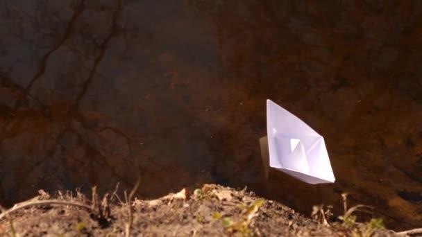 Weißes Papierboot, das sich im Wasser spiegelt, trägt die Strömung nach vorn.