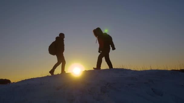Horolezců setkat na vrcholu zasněžené hory a užijte si jejich úspěch, zvedají ruce a radostně skákat. Muži turisté s batohy dosáhl vrcholu kopce v zimě za západu slunce. sportovní turistiky konceptu