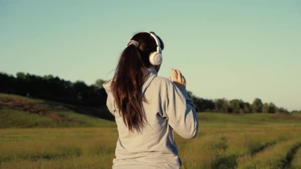 Free young woman trains in summer in park at dawn listens to music with headphones. Healthy beautiful girl is engaged in fitness, jogging in the country. Jogger girl breathes fresh air.