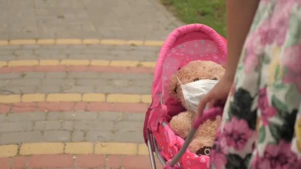 child plays an epidemic and protects toy. girl on street with his favorite toy in a protective mask. healthy childhood concept. little girl walks in park with a pram and a teddy bear in medical mask.