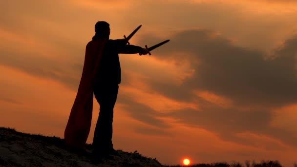 Egy győztes karddal a kezében és piros köpenyben áll egy hegyen a naplemente fényénél. A szabad ember szuperhőst játszik. a Római Légió játéka. szabad férfi lovag imádkozik kinyújtott karddal.