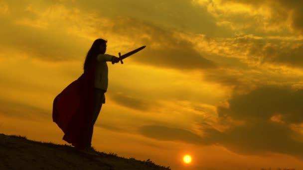 A lány római lenint játszik fényes napsugarakkal az ég ellen. Szabad női lovag. Szuper nő, karddal a kezében és vörös köpenyben áll a hegyen napnyugtakor. ingyenes nő játszik szuperhős.