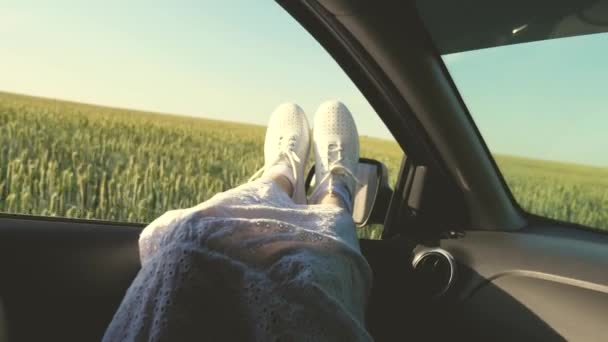 free woman travels by car. healthy Young woman enjoys traveling by car, protruding her legs from an open window. Legs of a girl in car window, riding car on country road past wheat field.travel