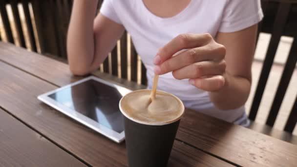 Egy lány egy kávézóban finom aromás kávét keverget és tablettát használ. egy nő kávét iszik és pihen. munka egy kávézóban és italban...