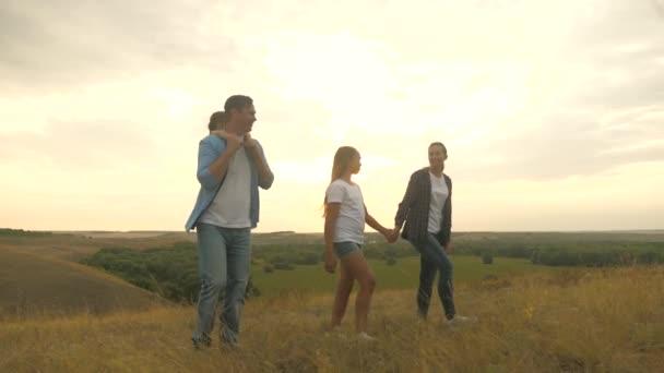 zdravá usměvavá rodina, držící se za ruce, procházející se po poli při západu slunce v horách, malá dcerka na tatínkově hřbetě. šťastné děti a rodiče procházka v paprscích krásného slunce, cestování na dovolenou