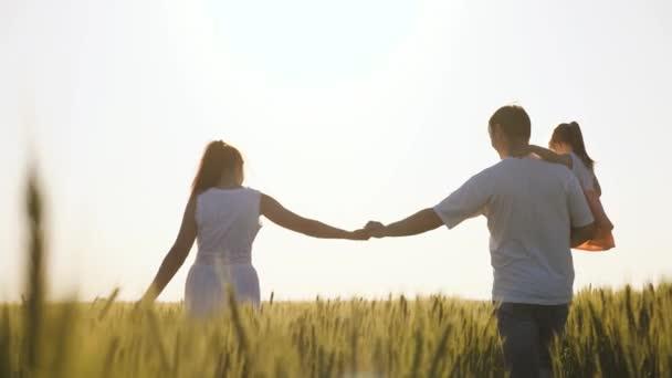 Šťastná rodina farmářů s dítětem, kráčí po pšeničném poli. Zpomal. Máma, táta a dítě jdou ruku v ruce. Zdravá matka, otec a malá dcera spolu užívají přírody, venku.