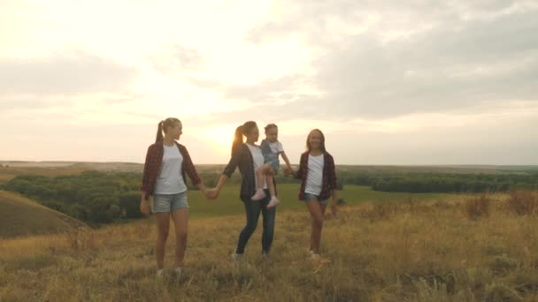 šťastné děti a rodiče procházet v paprscích krásného slunce, cestovat na dovolenou. zdravá usměvavá rodina držící se za ruce při procházce po poli při západu slunce v horách, dceruška v náručí matek.