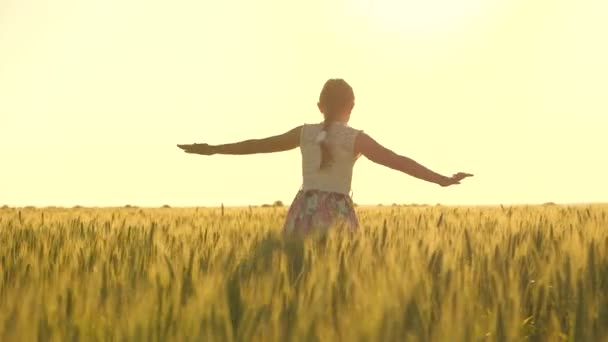 Free carefree girl enjoying nature and sunlight in a wheat field. happy childhood and family concept. healthy child runs and spins in slow motion across field, touching ears of wheat with his hand.