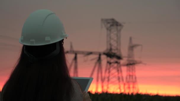 Eine Power-Ingenieurin mit weißem Helm inspiziert die Stromleitung mithilfe von Daten von elektrischen Sensoren auf einem Tablet. Hochspannungsleitungen bei Sonnenuntergang. Verteilung und Versorgung mit Elektrizität. saubere Energie