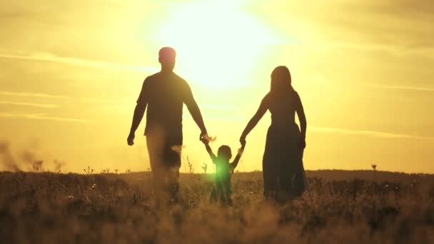 concept of happy family of children. healthy little daughter jumps and flies in arms of mother and father in a field at sunset. Happy family walks in park in sun. mom dad and baby walk outdoors.