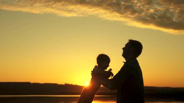 silueta otce a zdravého dítěte letícího nad sluncem. Táta vyhazuje svou šťastnou dcerku do vzduchu na pláž a baví se při západu slunce. Otec si hraje s dítětem ve vodě. šťastná rodina a dětství