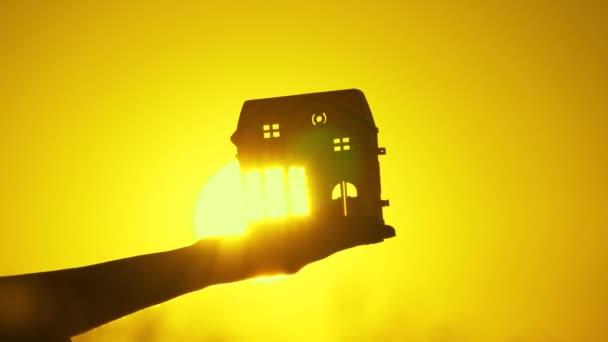 Ruční silueta s domečkem na hraní v paprscích teplého slunce, paprsky záblesků skrz okna a dveře. v dlaních dětského snu o svém domově. rodina krásný domácí koncept. krásná nemovitost při východu slunce.