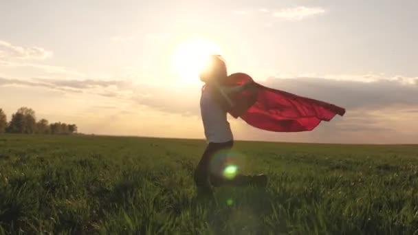 A tinédzser arról álmodik, hogy szuperhős lesz. fiatal lány piros köpenyben, álomszerű arckifejezéssel. Boldog szuperhős lány, zöld mezőn fut piros köpenyben, köpenyben röpköd a szélben. Játszik és álmodik. Lassú mozgás..