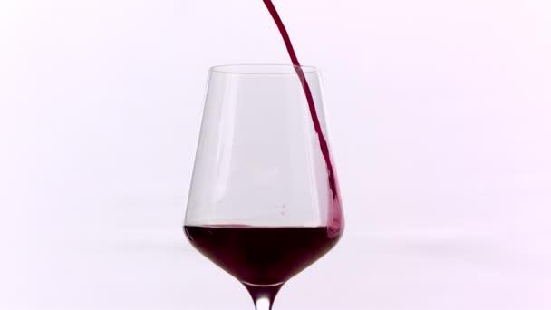 Červené víno nalílené do skla na bílém pozadí, pomalý pohyb