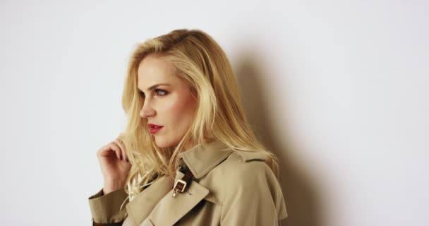 footage of beautiful blonde woman in trench coat and lingerie in front of white wall