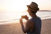 Silhouette des jungen männlichen Reisebackpacker mit Hut beim Fotografieren der sommerlichen Strandlandschaft gegen Sonnenuntergang - Reisebild Moment eingefangen Konzept.