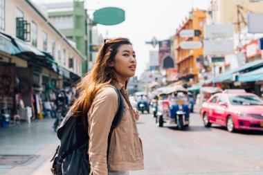 Young Asian female tourist backpacker walking on Khao San road during traveling to Thailand